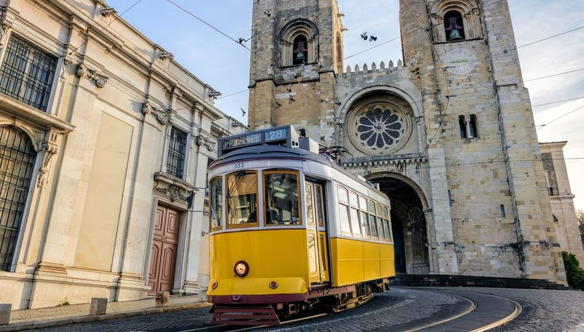 Yellow tram in front of Santa Maria cathedral in Lisbon, Portugal