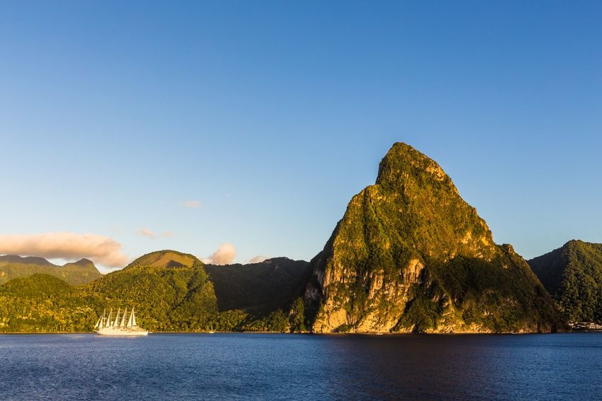 Coast of the island of St. Lucia with a boat with sails in the water