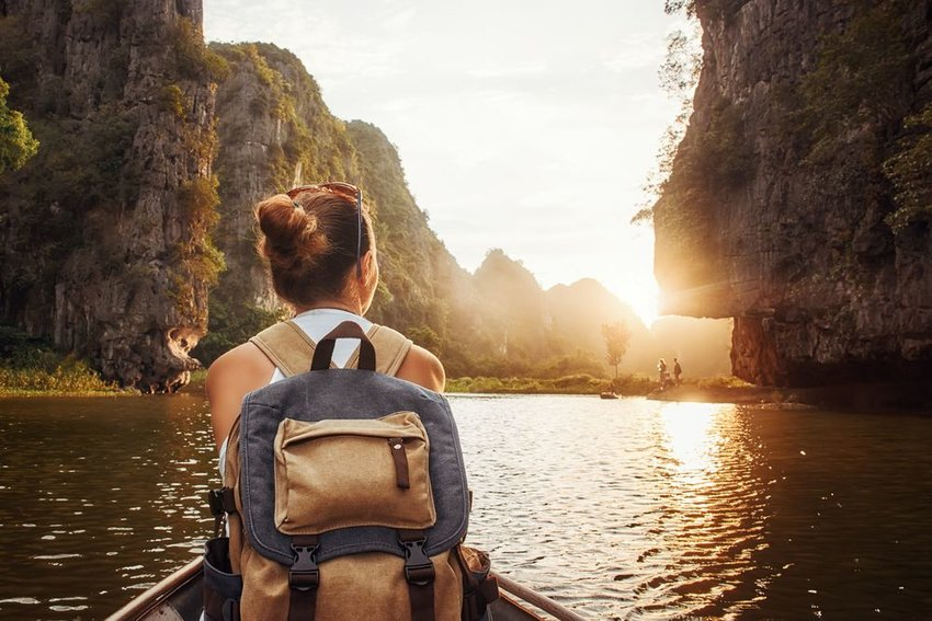 Woman sitting on front of boat with backpack on in Tam Coc, North of Vietnam