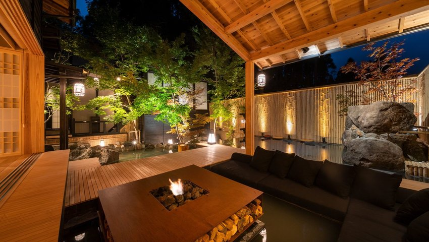 Exterior view of sitting area around fire pit in covered deck area