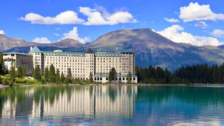 The Fairmont Chateau on Lake Louise with trees surrounding and mountains in background
