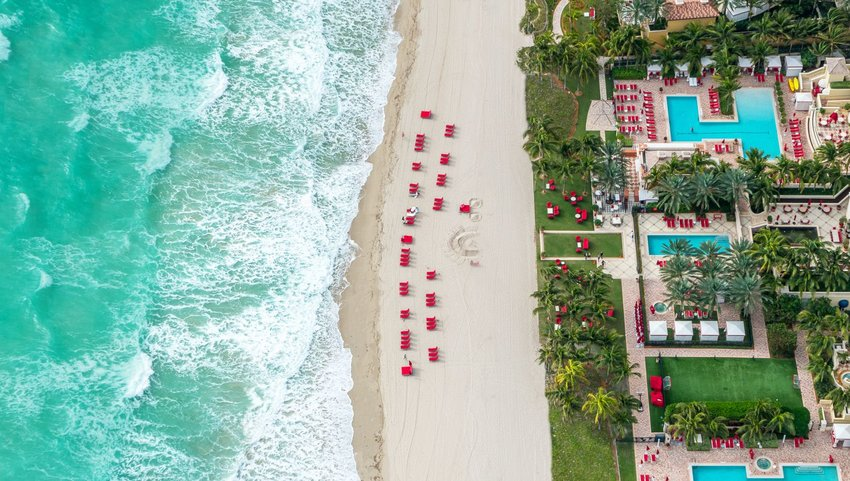 Aerial view of beach lines with red lounge chairs and hotel pools