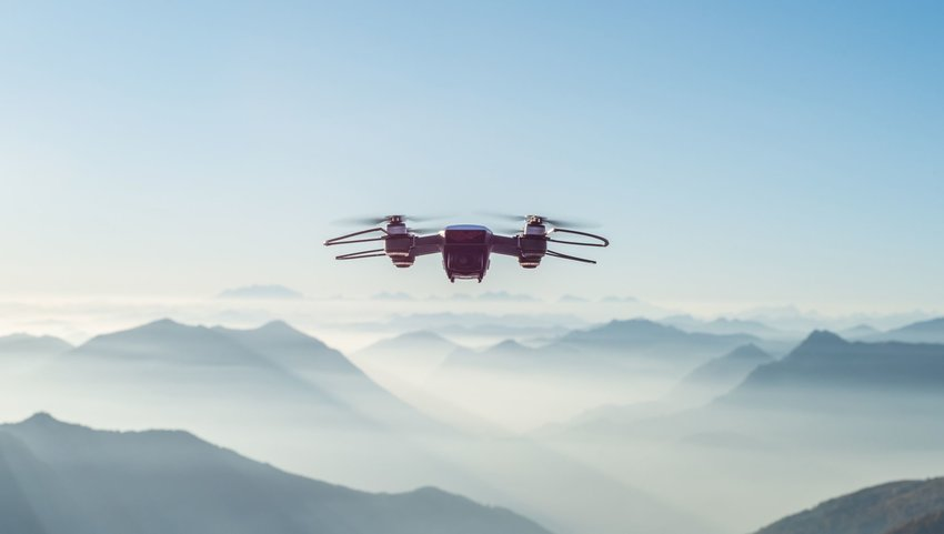 Drone in sky with mountain ranges in background