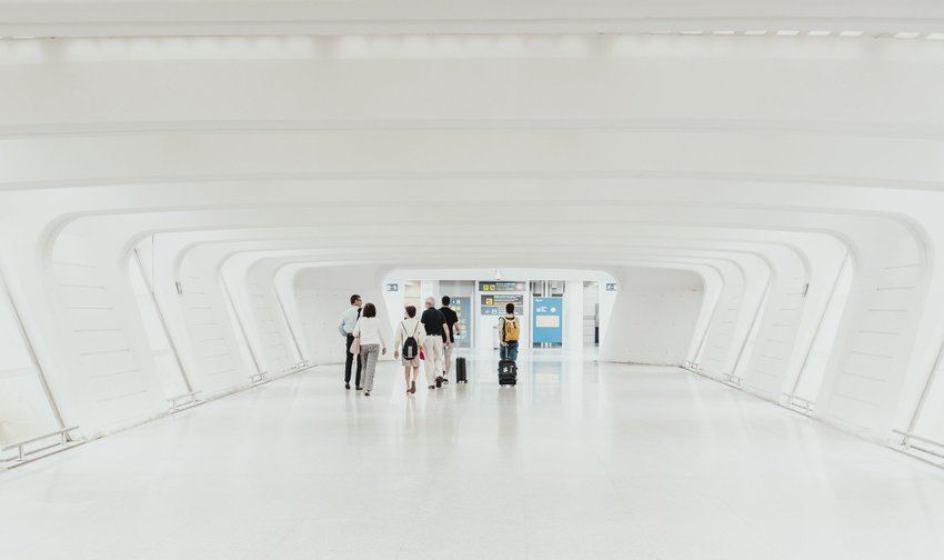 Group walking together through white hallway in airport