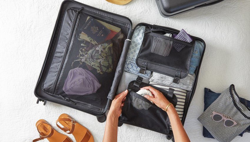 Person packing clothes into a suitcase