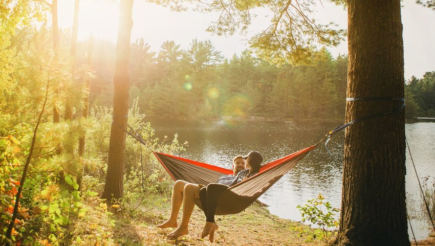 Two people relaxing and talking in a hammock