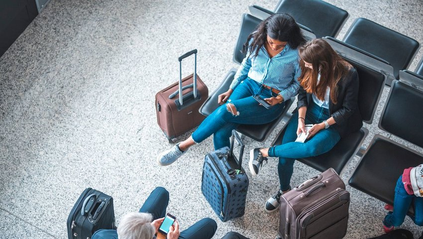 Two women looking at phone while sitting in airport chairs surrounded by luggage