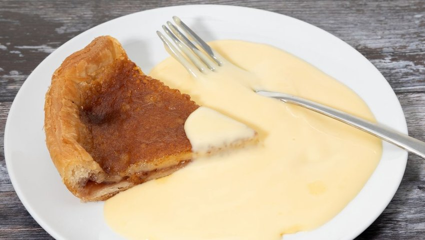 Bakewell pudding on white plate with custard