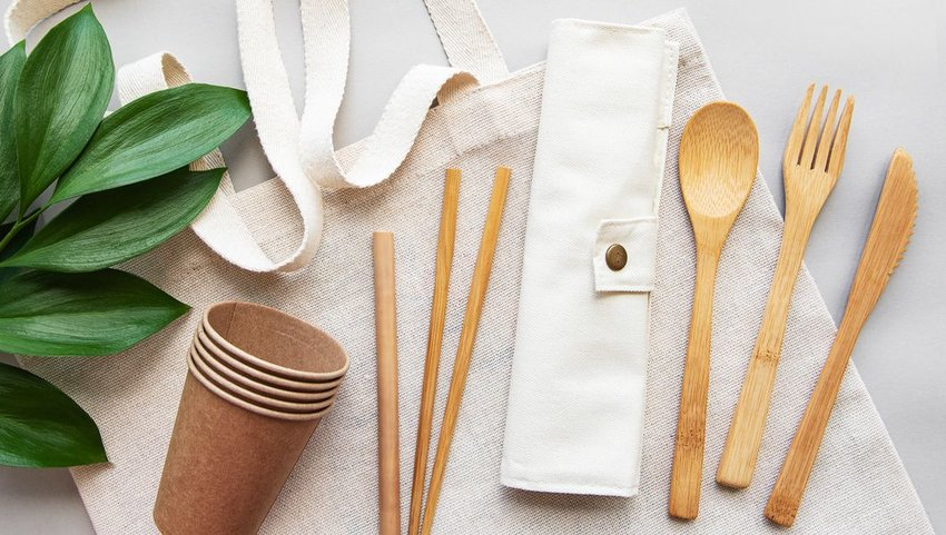 Bamboo eating utensils, straws and cups on a canvas bag