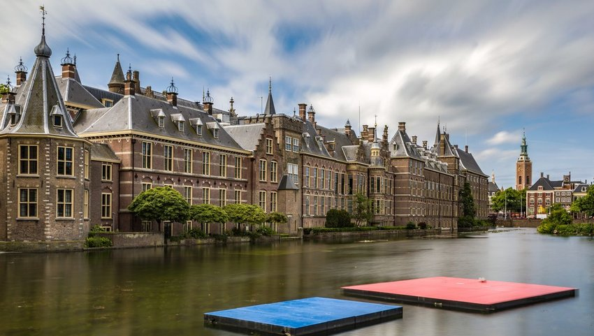 Exterior view of Het Binnenhof with water in front on cloudy day