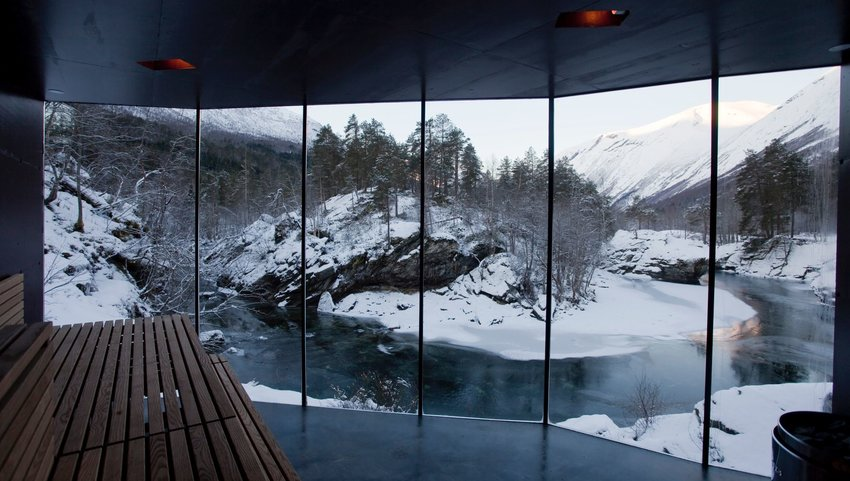 Large floor to ceiling windows in a spa with views of a river and mountainous landscape covered in snow