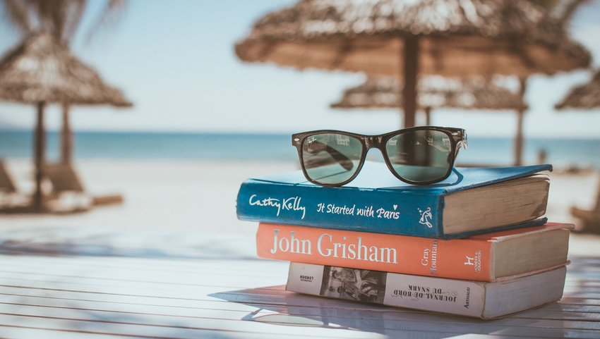 Stack of books with sunglasses on top at the beach