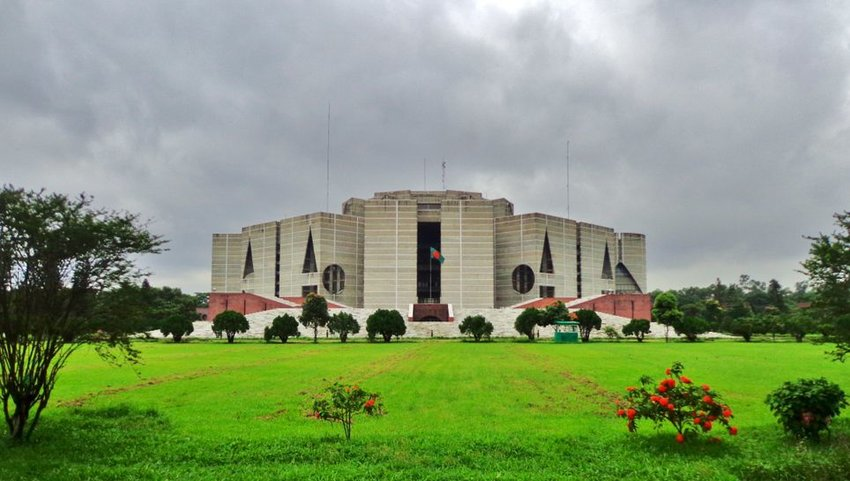 National Parliament House on cloudy day with green grass in front