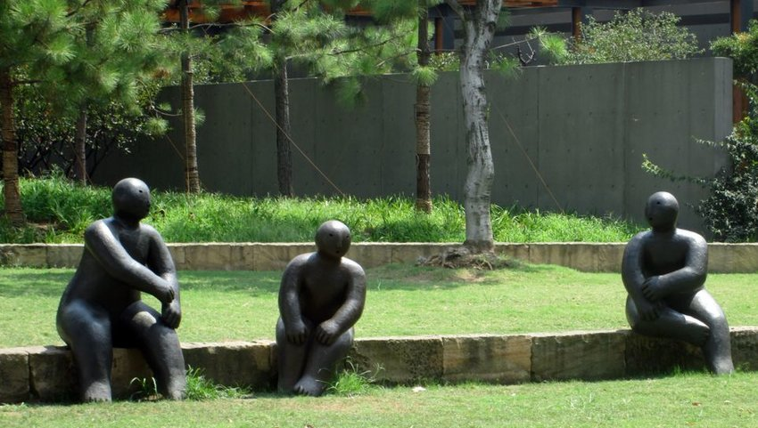 Three statues sitting on a ledge in a park