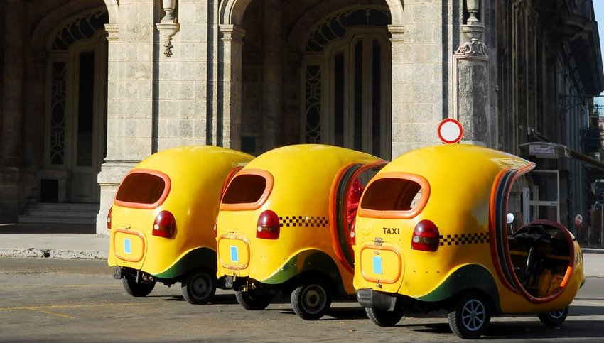 Three yellow Cocotaxis in a row in Havana