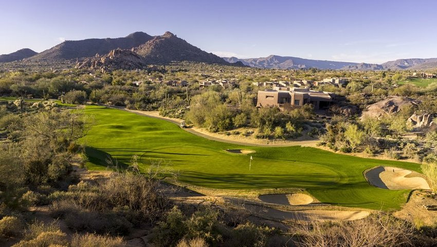 Overhead view of golf course with mountains in distance