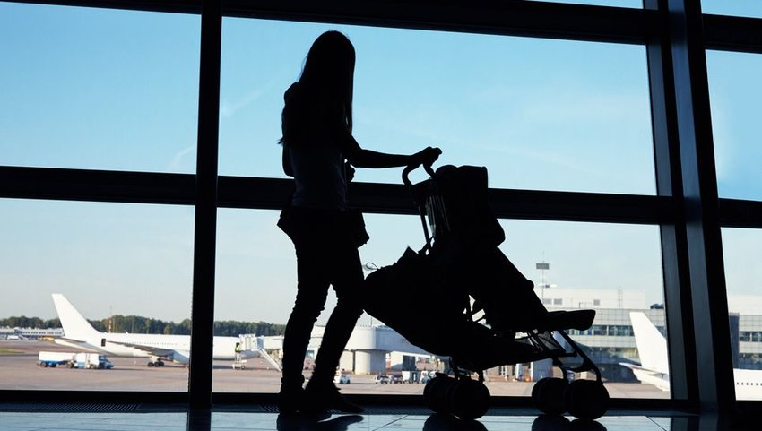 Silhouette of person standing in airport with baby stroller