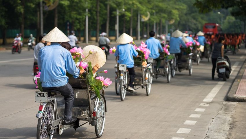 Cyclo drivers wearing hats on Hanoi street with passengers