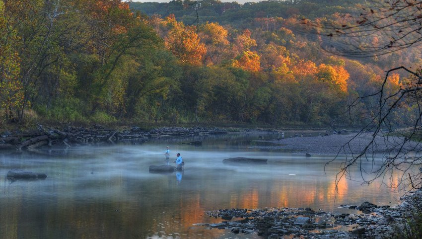 Two people fishing in a river with fall colored trees