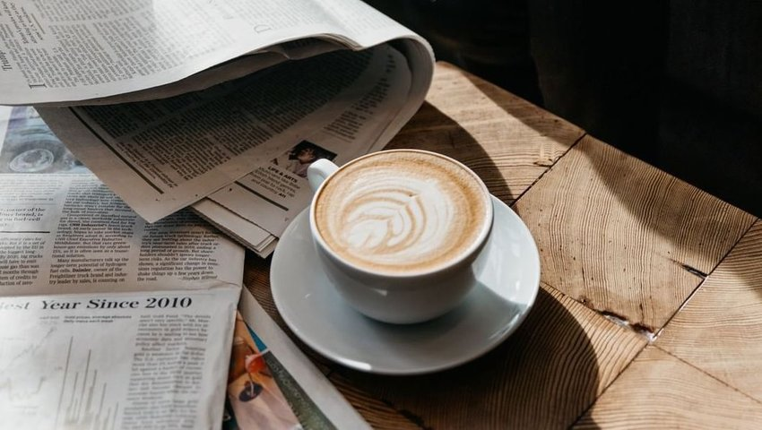Mug of coffee on wooden table with newspapers