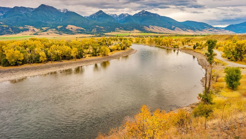 Yellowstone river running through Yellowstone National Park with mountains in background