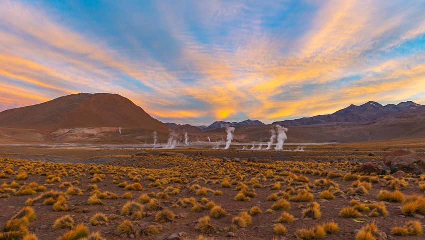 El Tatio geyser with mountains in distance at sunset