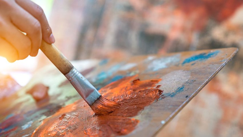 Person painting with orange paint