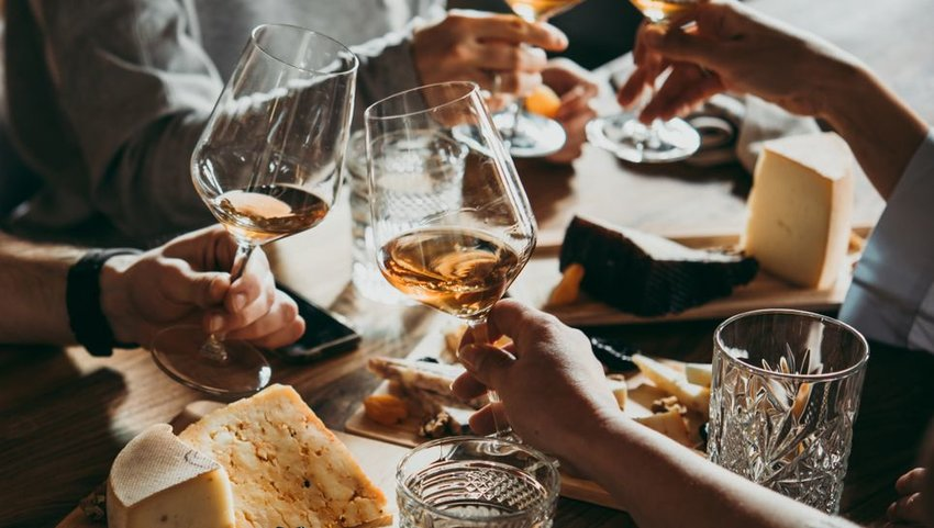 People drinking wine with cheese on boards