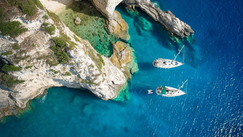 Sailboats next to cliffs in Greece