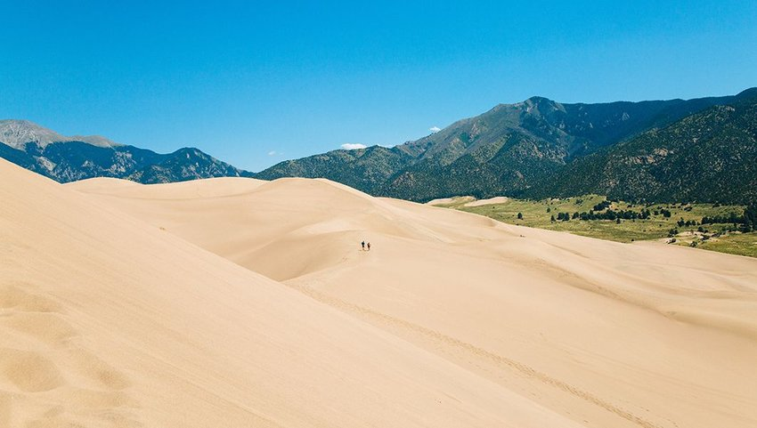 Two people walking on a sand dune in the distance at Great Sand Dunes National Park and Preserve