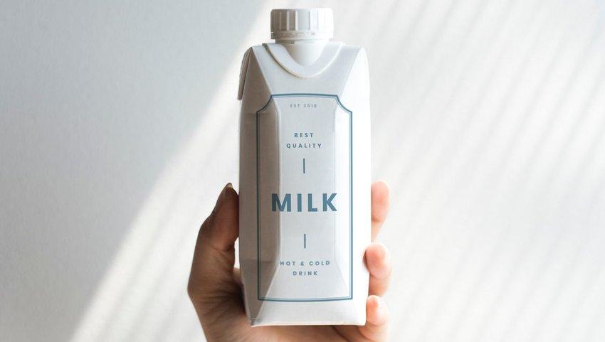 Person holding a carton of milk