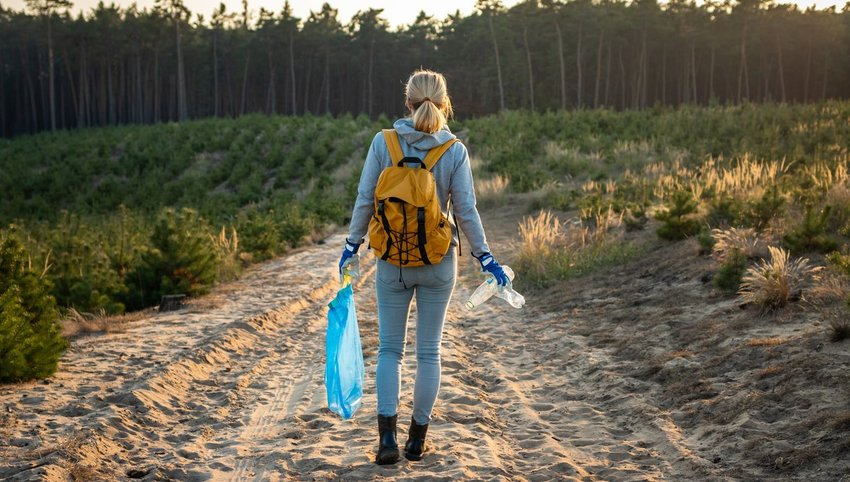 Woman picking up trash on trail in nature