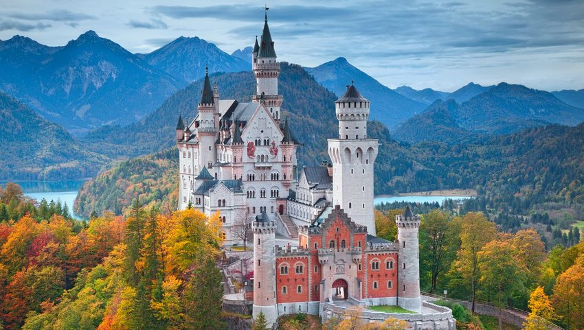 Neuschwanstein Castle on an autumn day with mountains and lake in background