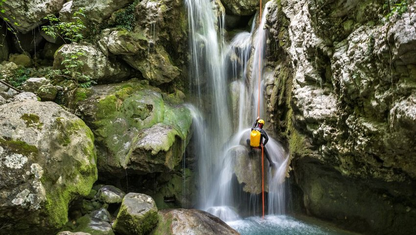 Person canyoneering down a waterfall