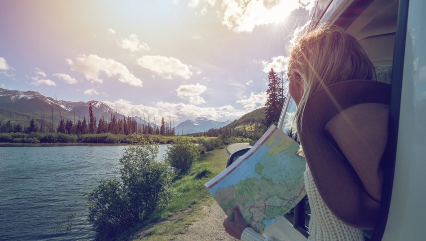 Woman leaning out of car with map looking out at lake and mountains