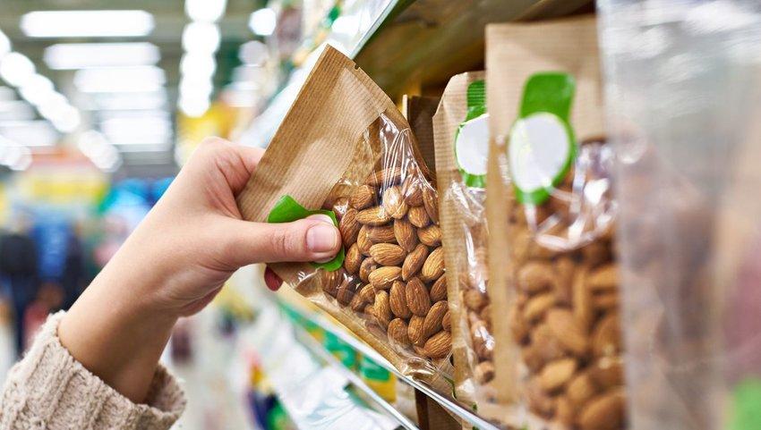 Person grabbing bag of almonds off shelf