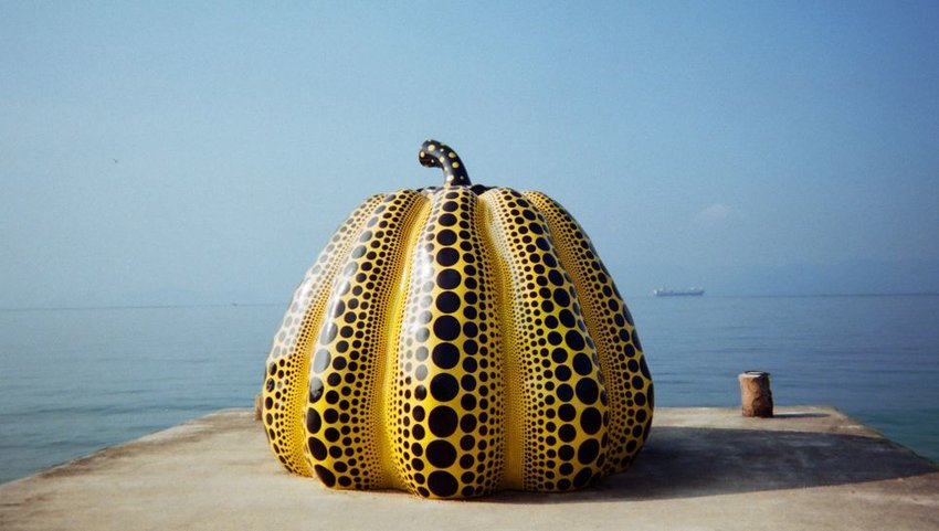 Yellow pumpkin sculpture on end of pier with ocean behind