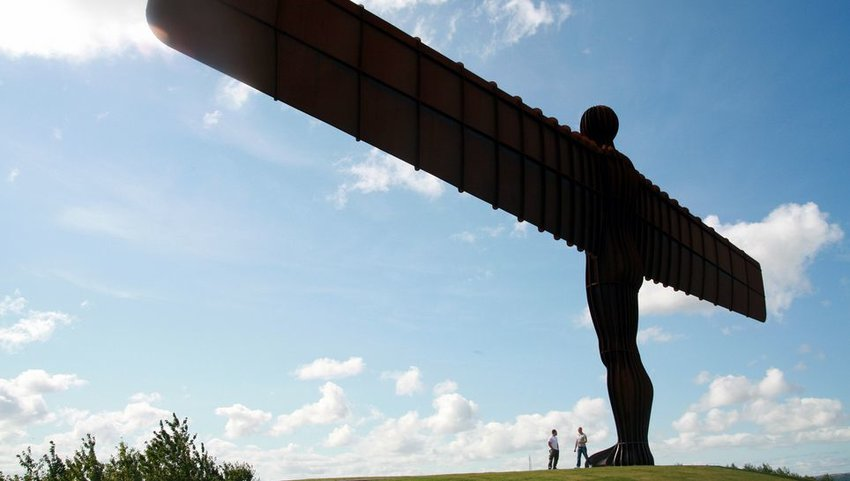 Two people standing at the foot of the Angel of the North, located in Northumberland