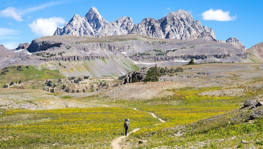 Person hiking down the Teton Crest trail with backpack on